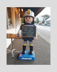 Life-size Playmobil Man on footpath offing hand sanitiser. Image Source: K Ross