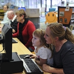 woman and child looking at a computer screen